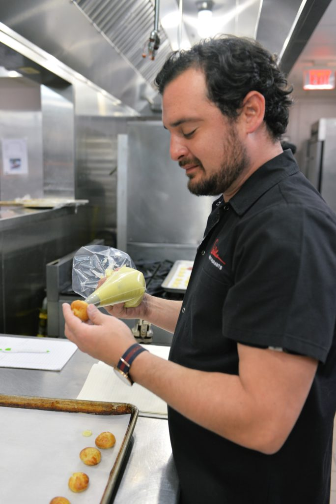 David Cordua fills profiteroles with pastry cream. Photo by Dragana Harris
